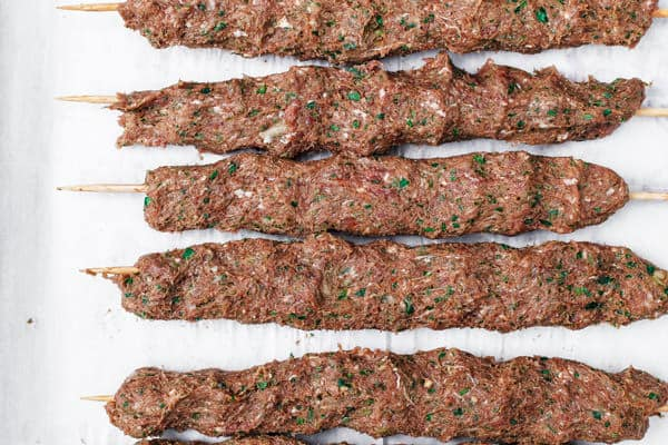 Raw kofta kebabs assembled on tray before grilling