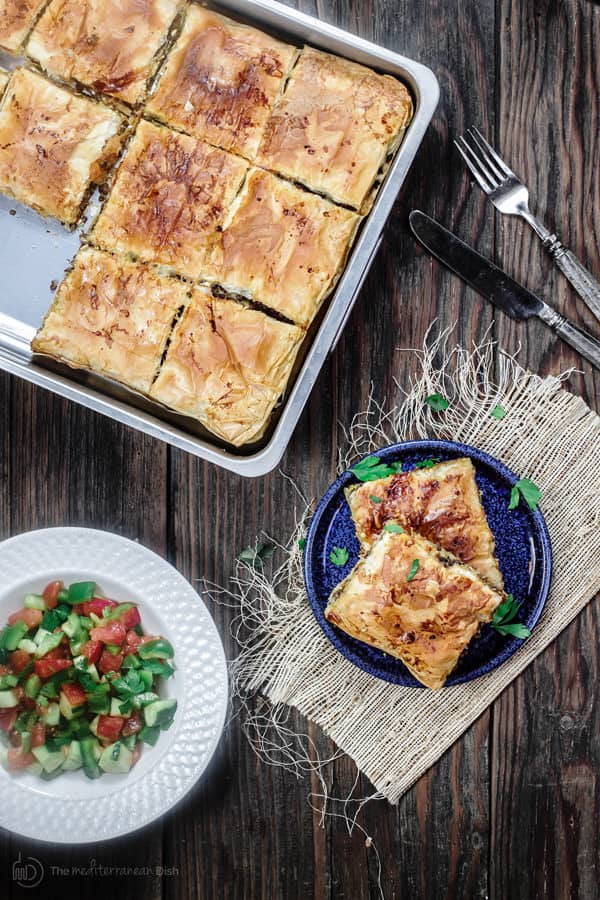Slices of Phyllo Meat Pie in a pan served with peppers, cucumbers and tomatoes