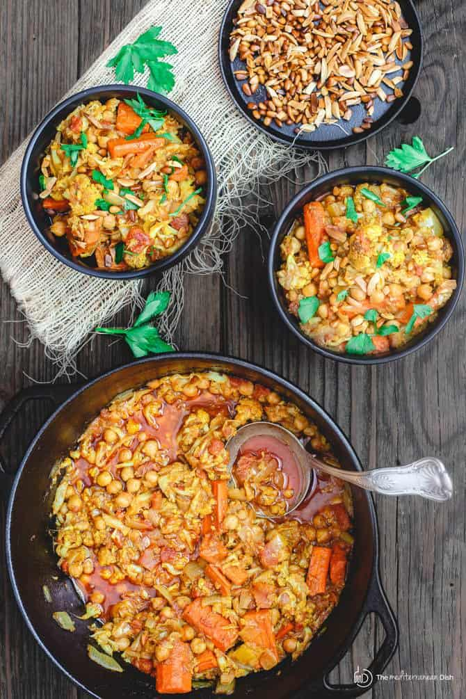Roasted Cauliflower and Chickpea Stew in bowls with extra roasted nuts served on the side