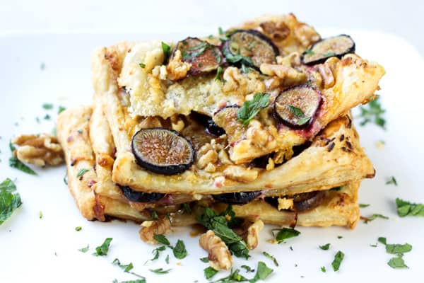 Layers of fig puff pastry garnished with walnuts and fresh parsley