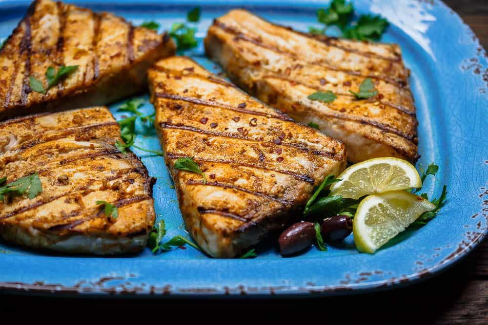 Close-up of Grilled Swordfish served with olives and a lemon slice