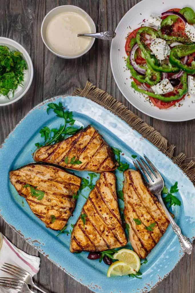 grilled swordfish served with greek salad and a side of tahini
