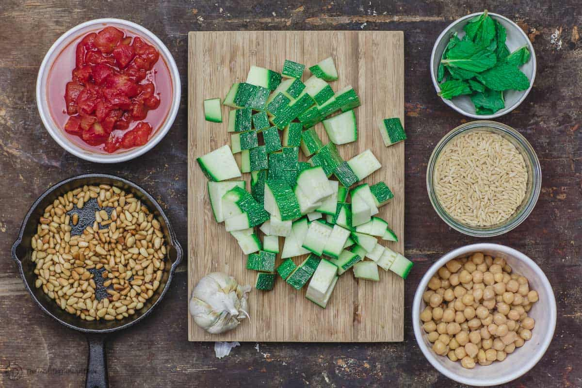 Ingredients for orzo recipe. zucchini, chickpeas, tomatoes, orzo, fresh mint, garlic and toasted pine nuts