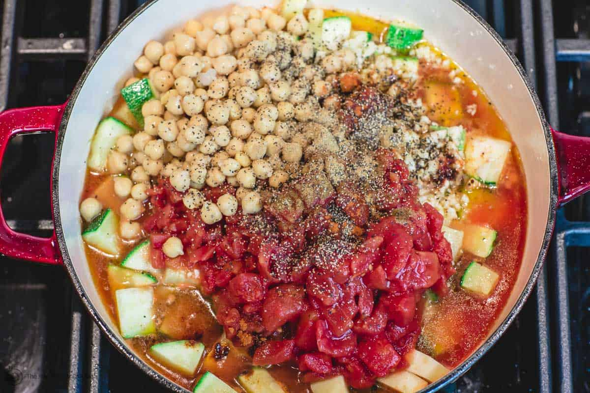 Garlic, chickpeas, tomatoes and spices are added to skillet
