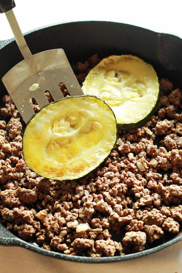 Cooked zucchini slices added to pot of browned ground beef