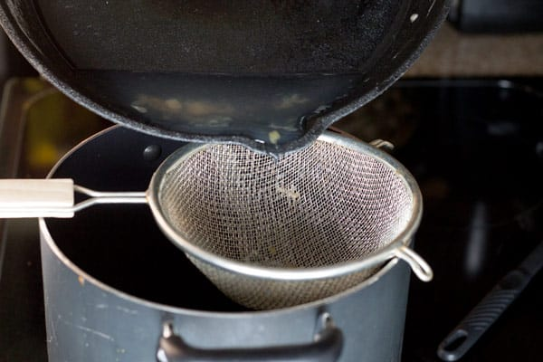 Pouring broth into the pot using a strainer