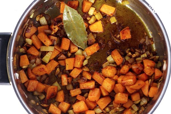 Pot containing olive oil, onions, sweet potato and celery