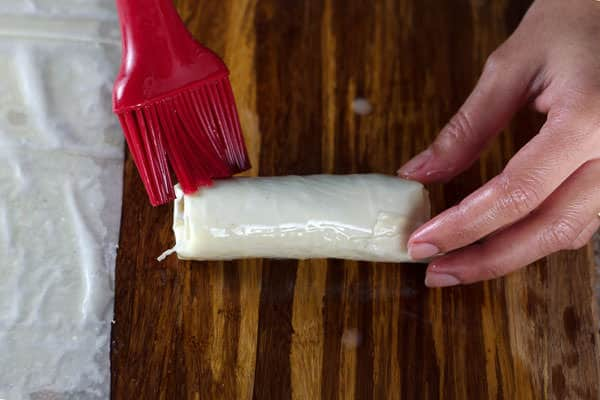 Brushing meat rolls with egg wash