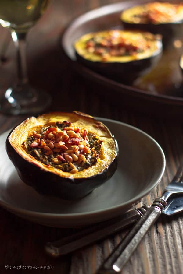 Stuffed Acorn Squash Recipe | The Mediterranean Dish. Acorn squash roasted and stuffed with feta, spinach, pancetta and more! The perfect Thaksgiving recipe.