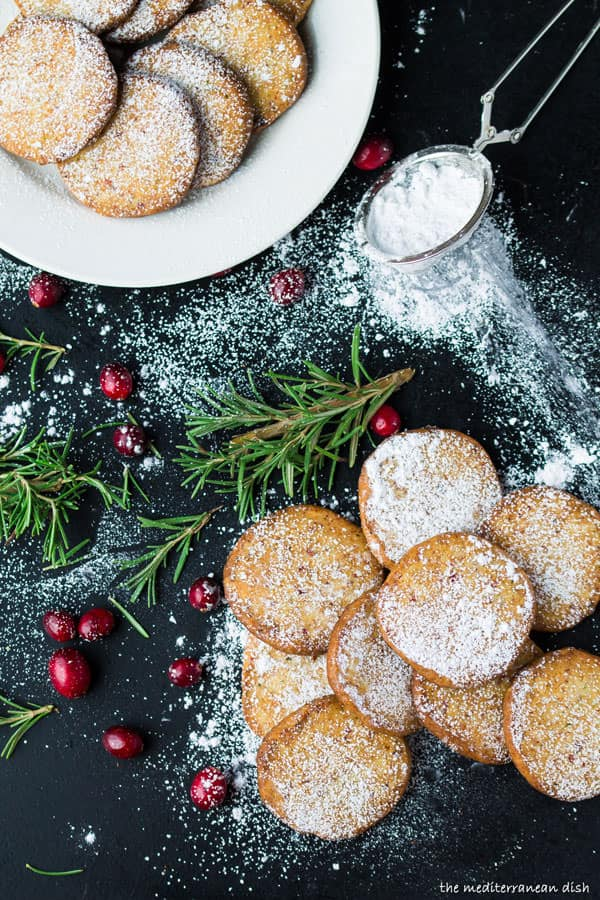 Cranberry Parmesan Shortbread Cookies with Powdered Sugar and a garnish of cranberries and rosemary