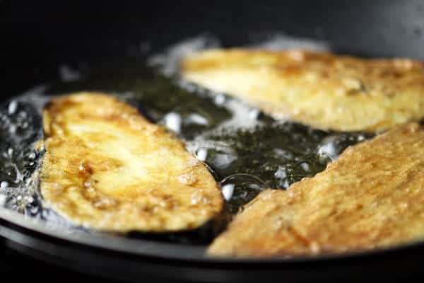 Eggplant being fried in a pan