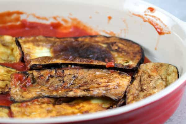 Fried eggplant slices placed in a cooking dish on top of a layer of tomato sauce