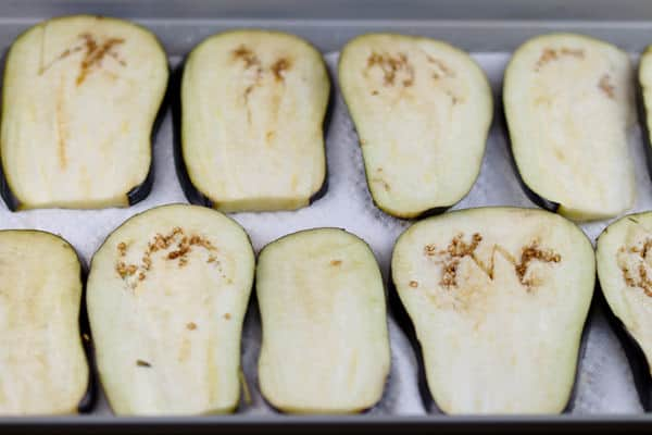 Slices of eggplant laid out on a baking sheet