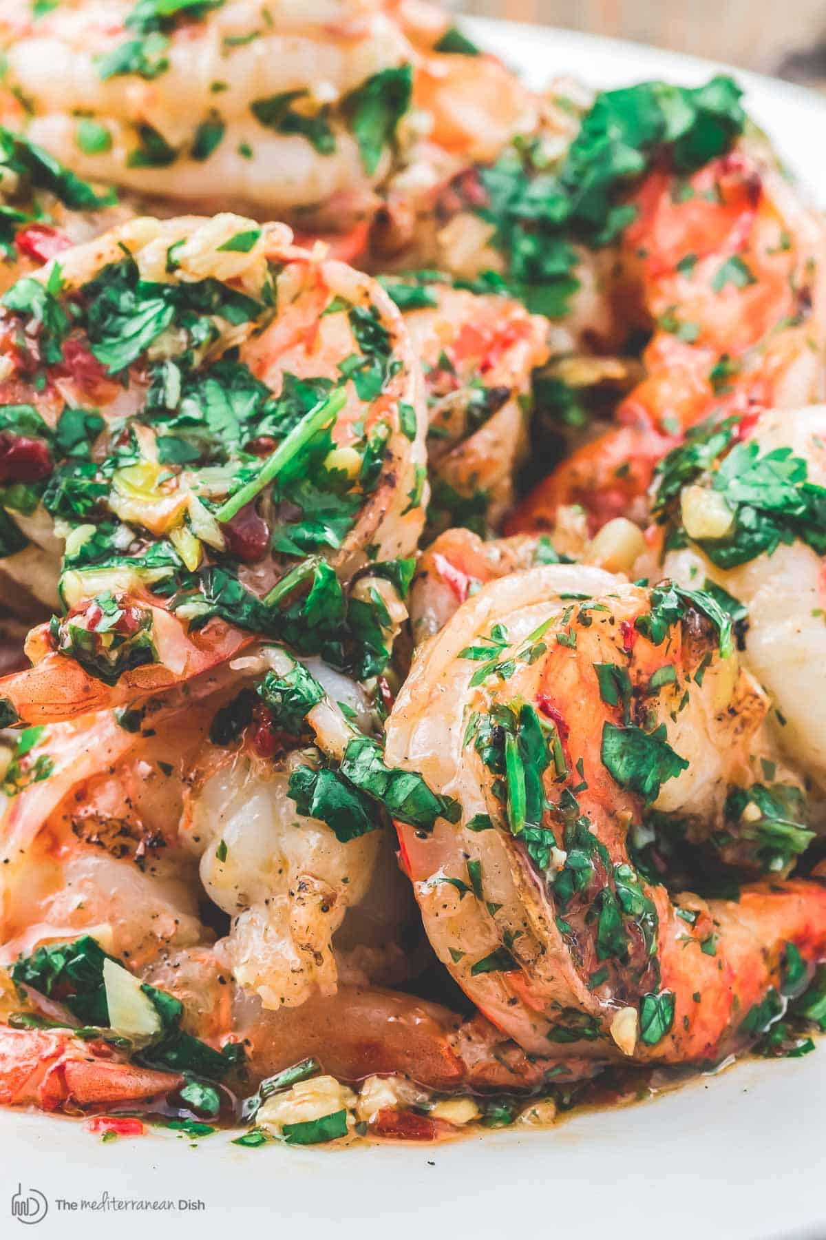 Grilled shrimp tossed in roasted garlic cilantro sauce served on a plate.