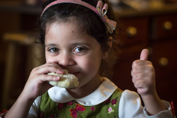 Girl eating a piece of bread giving a thumbs up