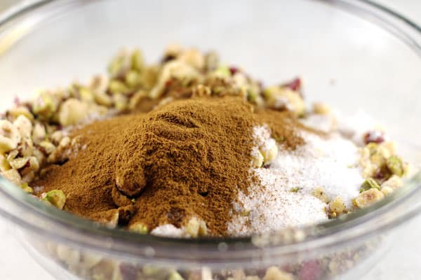 Sugar, ground cinnamon, and ground cloves added to bowl of nuts