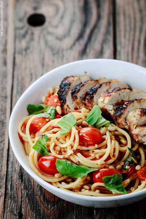 Bowl of spaghetti and slices of blackened chicken