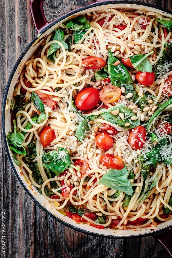 Pot of spaghetti topped with fresh basil, grape tomatoes, pine nuts and grated cheese