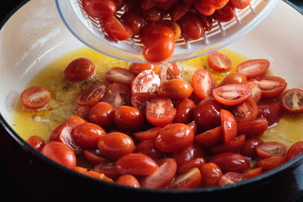 Cherry tomatoes being added to a pot with oil