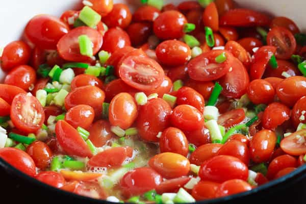 Cherry tomatoes cooking in a pot with oil and green onions