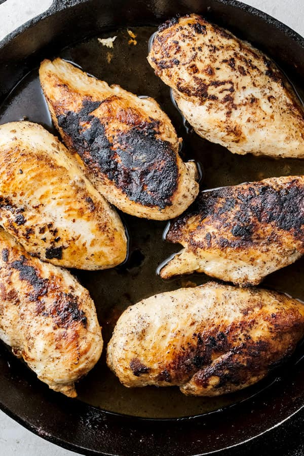 Chicken breasts being cooked in a skillet