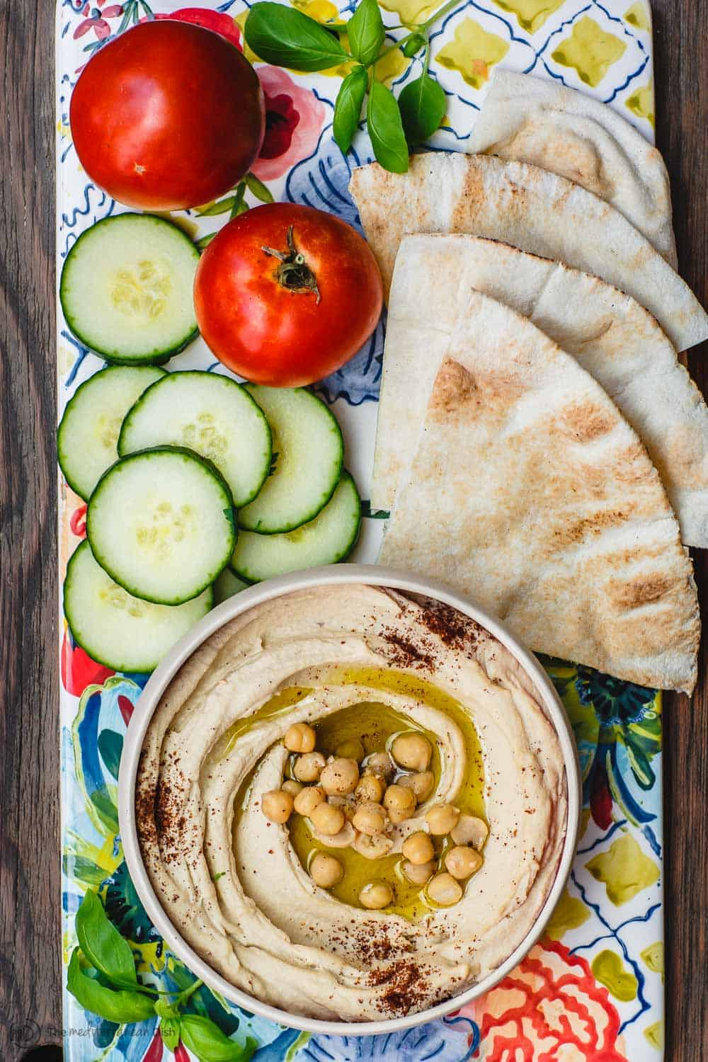 Classic creamy hummus served with olive oil, vegetables and pita