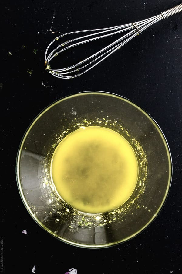 Bowl containing vinegar, olive oil and honey whisked together.