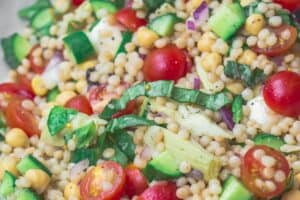 Mediterranean Couscous Recipe | The Mediterranean Dish. Think the best ever couscous salad! Toasted pearl couscous loaded with fresh chopped veggies and other Mediterranean favorites like chickpeas, olives and artichokes. A zesty lime vinaigrette brightens it even more! See the recipe on TheMediterraneanDish.com