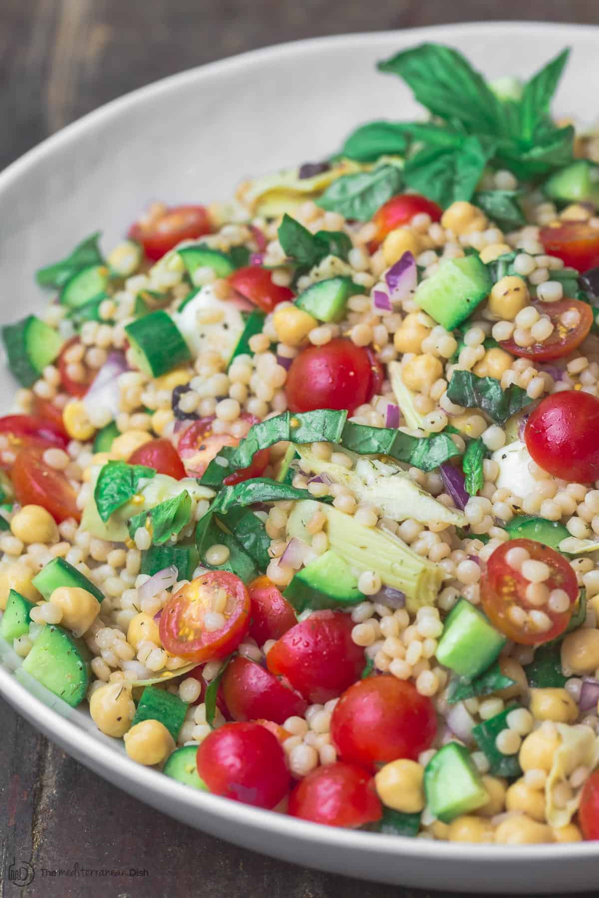 Mediterranean pearl couscous salad served in large bowl
