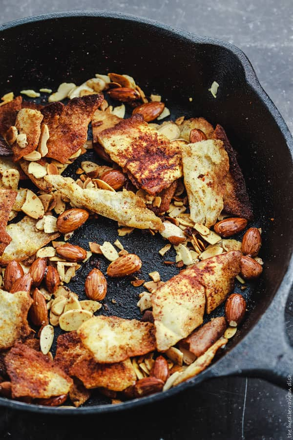 Skillet with pieces of pita bread and sliced almonds