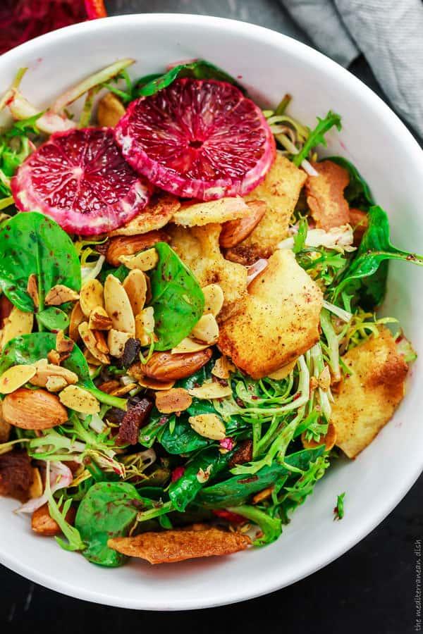 Frisee spinach salad garnished with blood orange slices