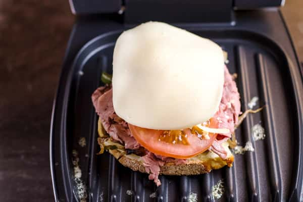 Assemble the components on a table-top grill, including the bread, roast beef, tomato, vegetables and cheese
