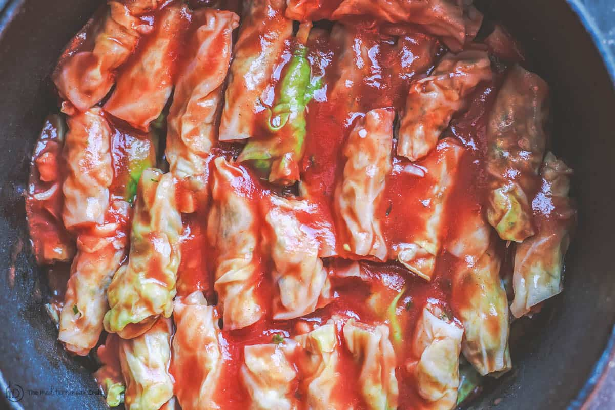Vegetarian stuffed cabbage rolls layered in large pot with tomato sauce