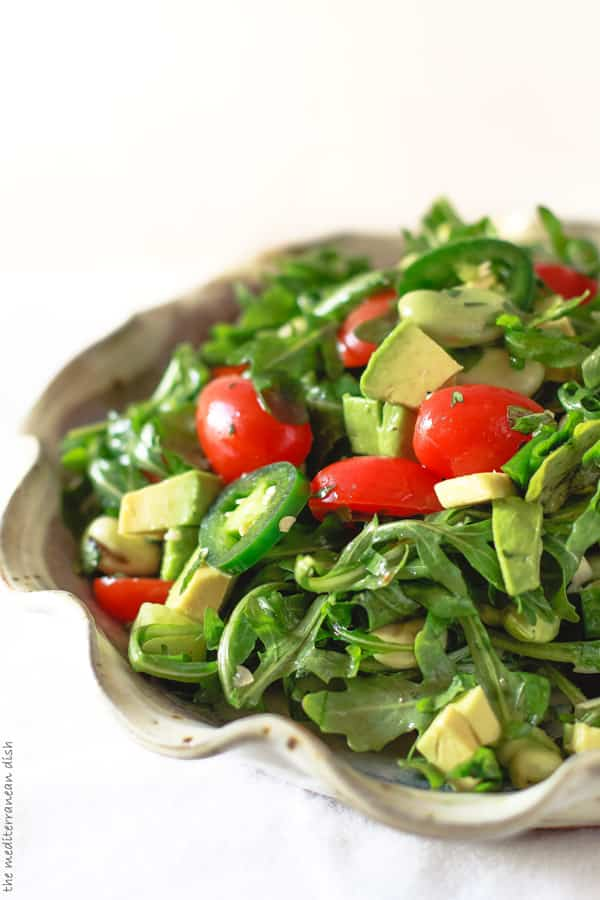 Bowl of Arugula salad with avocados, fava beans and garlic herb vinaigrette