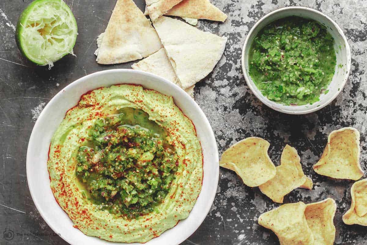 Avocado hummus bowl and a bowl of salsa verde with chips to serve