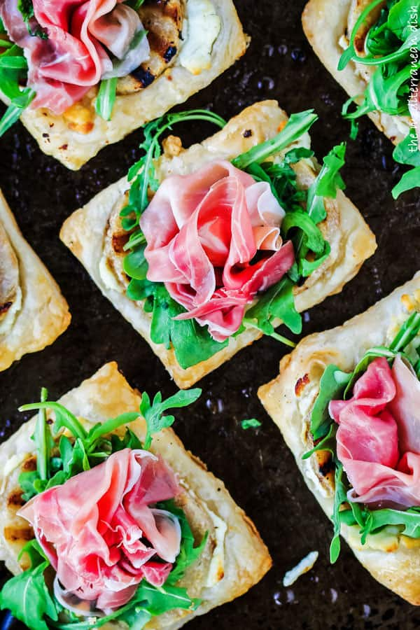 Easy puff pastry topped with grilled pears, prosciutto and goat cheese from The Mediterranean Dish. Get this all-star recipe today! It will win your guests heart at the first bite!