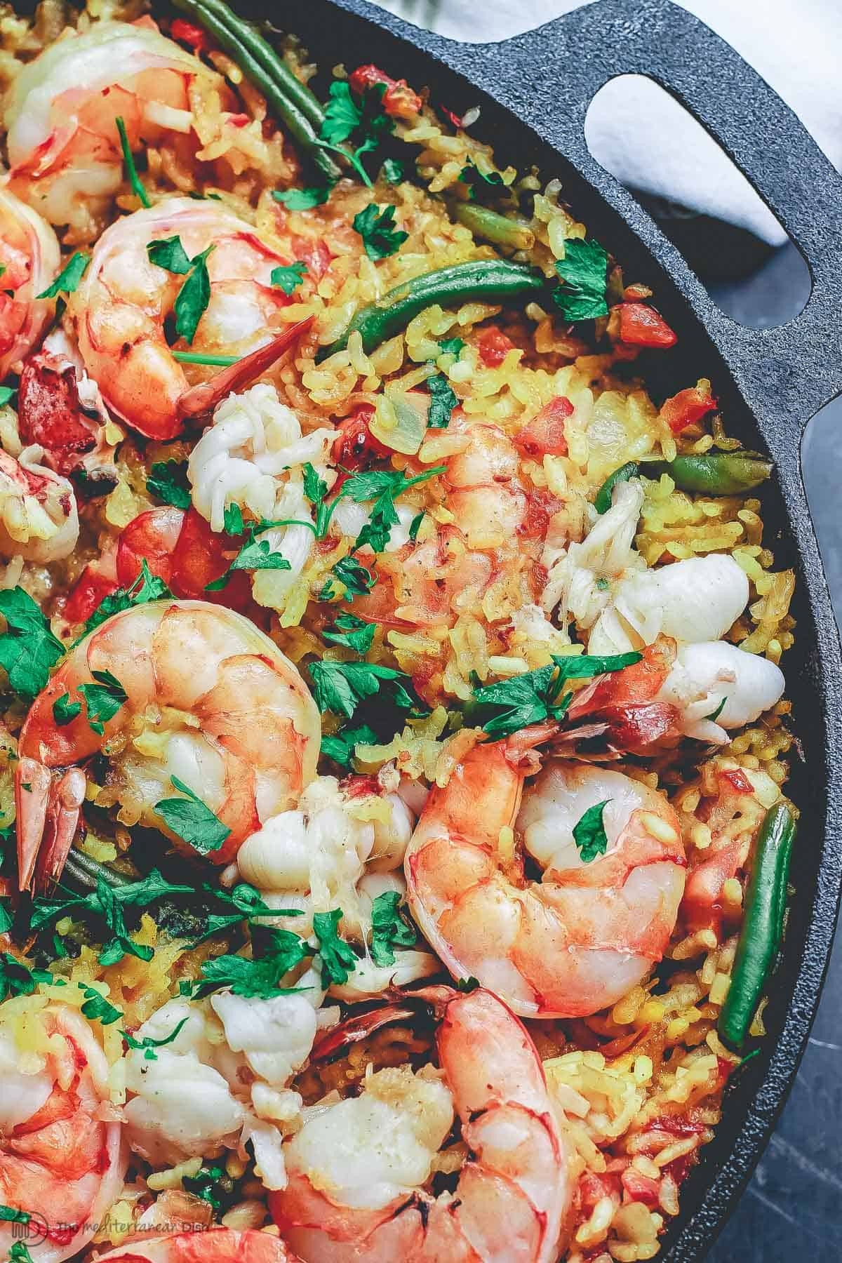 Seafood Paella made with lobster and shrimp in cast iron skillet