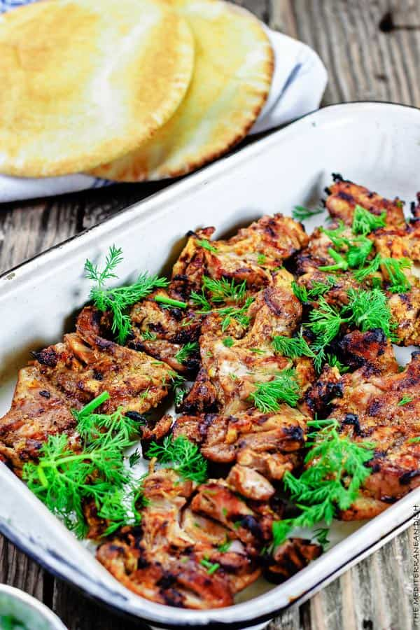 Dish of Mediterranean Grilled Chicken served with pita bread on the side