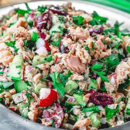 Mediterranean Tuna Salad with fresh herbs, chopped vegetables and Dijon vinaigrette on a plate
