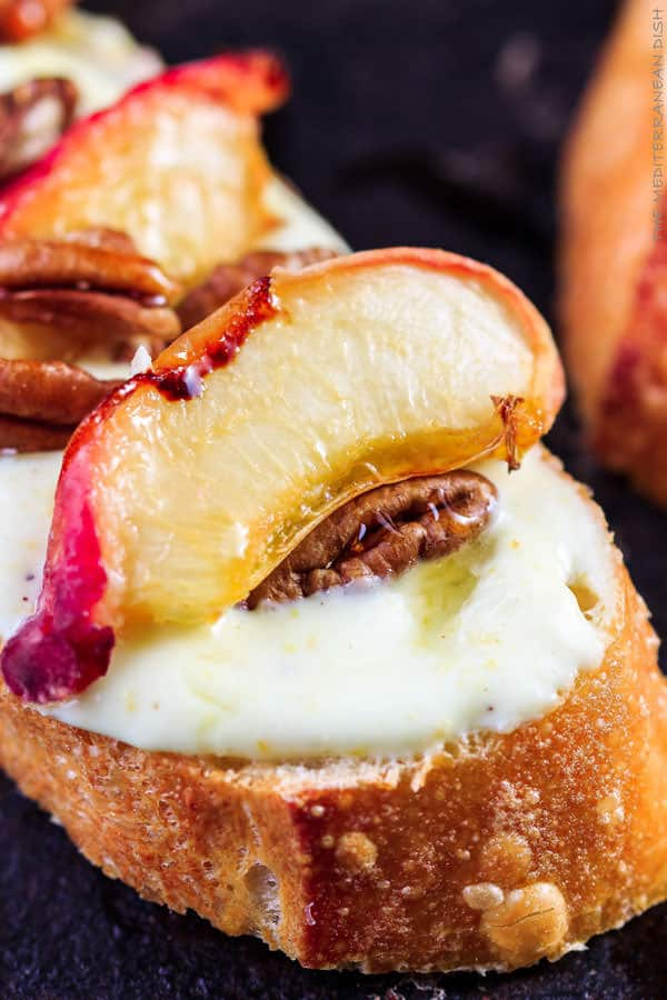 Roasted Peaches and Orange Whipped Greek yogurt crostini | The Mediterranean Dish. An easy recipe that will satisfy the sweet tooth in all of us. Serve these crostini for brunch or dessert!