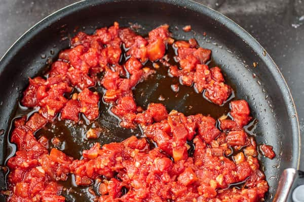 Canned diced tomatoes added to a pan with garlic and oil