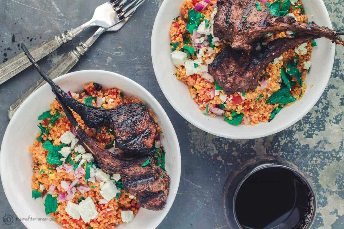 Two servings of Lamb chops over mint quinoa.  Served with a glass of wine