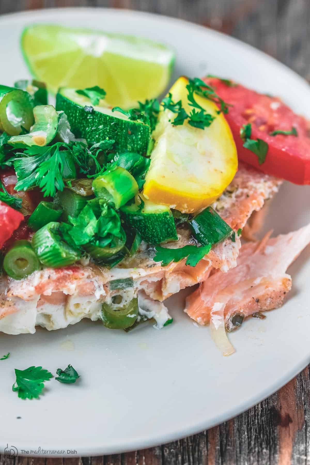Close-up of salmon served with vegetables, lemon wedge and garnished with fresh parsley