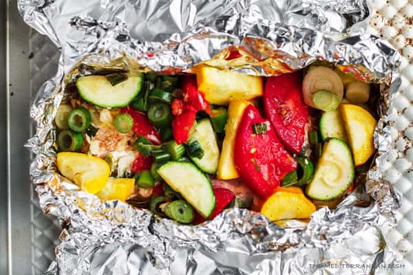 Mediterranean-style Oven Baked Salmon in Foil | The Mediterranean Dish. Salmon with garlic and thyme, topped with vegetables and a buttery-lime sauce and baked in foil to perfection! Bakes in less than 25 mins! Try this easy dinner soon.