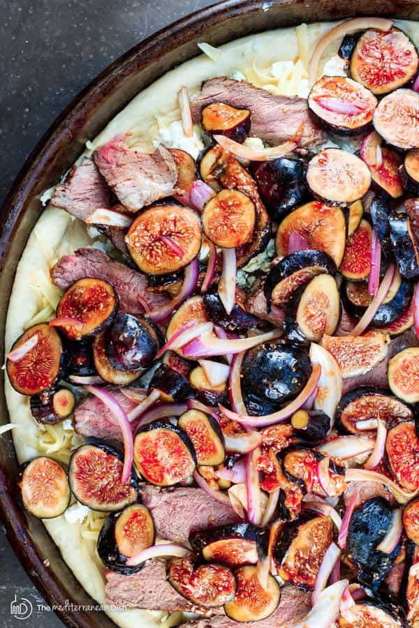 Homemade Pizza with Three Cheeses, Steak and Figs | The Mediterranean Dish. Ditch take-out and try this easy homemade pizza with steak, figs, kale and three different cheeses! It's homemade pizza like you would eat at Mediterranean pizzeria! Step-by-step photos included!