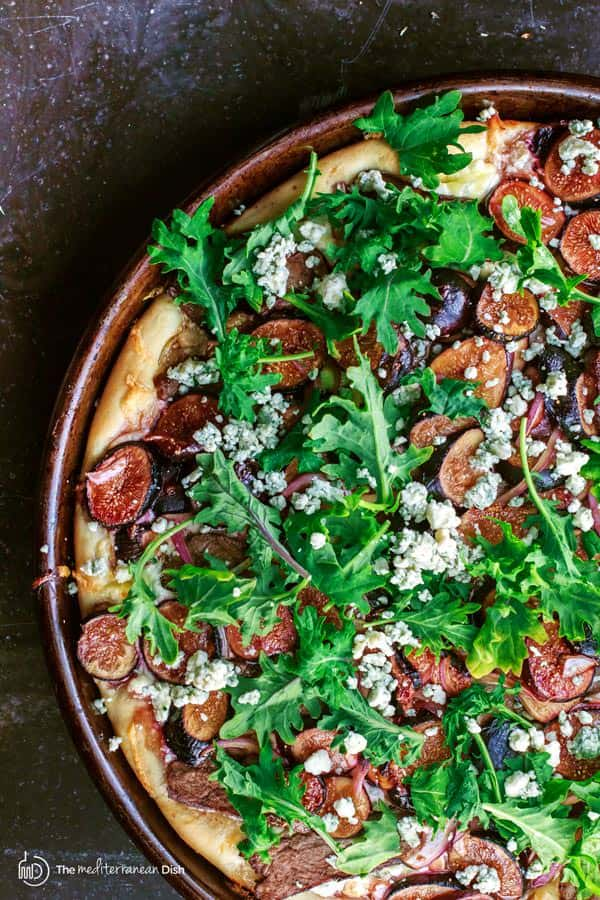 Fresh greens added to top of meat, cheese and figs