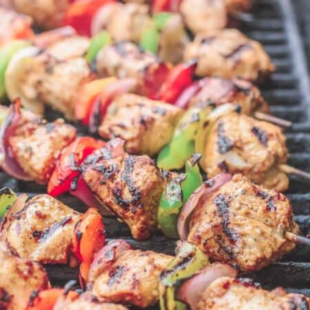 Chicken kabobs arranged on an open-flamed grill