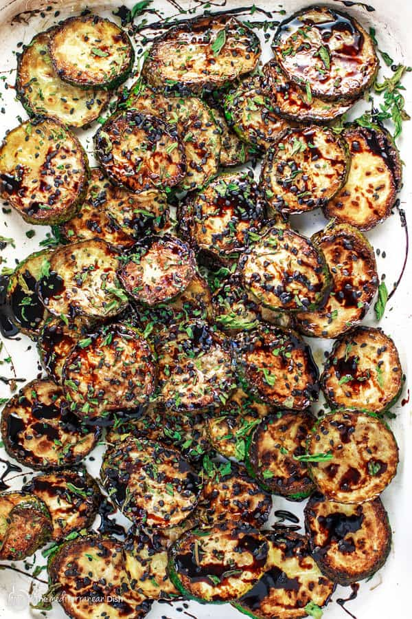 Easy Skillet Zucchini Recipe with Balsamic Reduction | The Mediterranean Dish. This is simply the best side dish! Zucchini rounds sauteed in olive oil and finished with a sweet balsamic reduction, black sesame seeds and a sprinkle of mint flakes. Perfection in minutes!