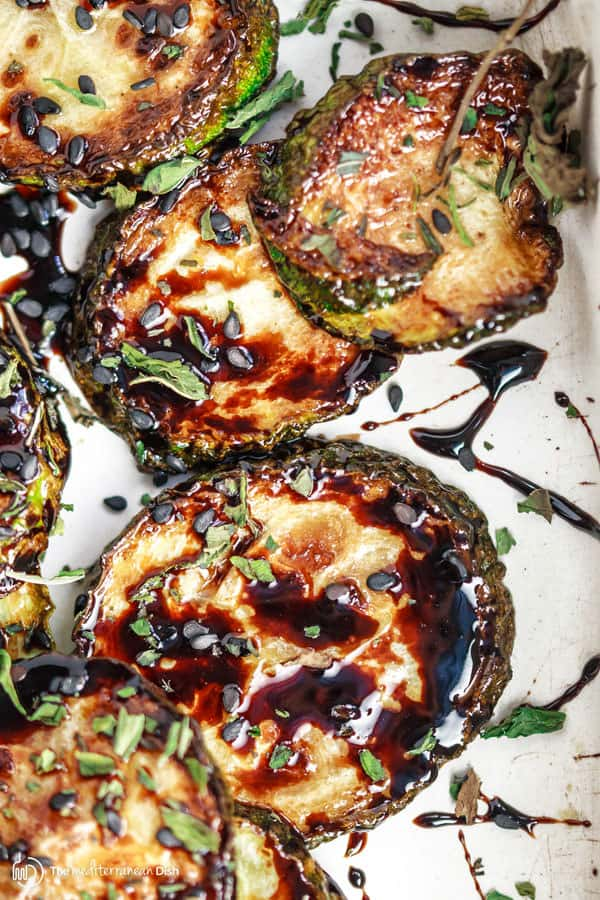 Close up of prepared zucchini rounds drizzled with balsamic reduction ready to be served