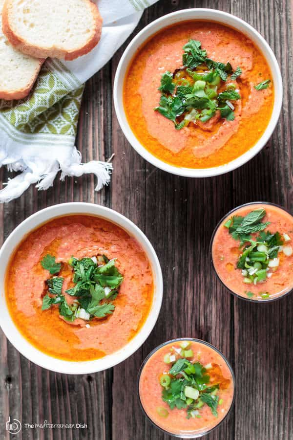 Easy Tomato Gazpacho Recipe | The Mediterranean Dish. Fresh, crisp and flavor-packed! You can make it in 15 minutes! Blend super ripe tomatoes with other chopped fresh vegetables, garlic and spice. Chill then add olive oil and a little herb garnish. And just like that, dinner is served! Or serve it as a party appetizer in small cups or even shot glasses!